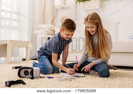 Joyful brother and sister are playing tic-tac-toe in living room. They are sitting on floor and laughing
