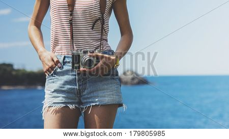 Tourist traveler photographer making pictures seascape on vintage photo camera on background yacht and boat piar hipster girl enjoying peak mountain and nature holiday mockup ocean waves view blurred backdrop