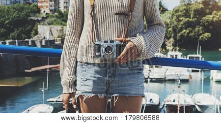 Tourist traveler photographer making pictures sea scape on vintage photo camera on background yacht and boat piar hipster girl enjoying peak mountain and nature holiday mockup ocean waves view blurred backdrop