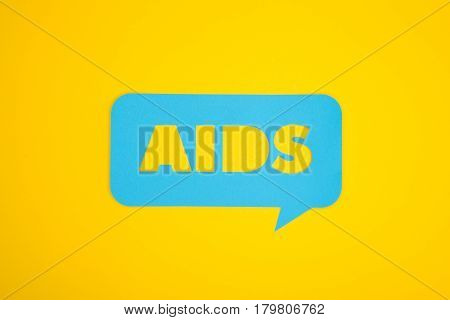 The AIDS word cut in a blue cardboard bubble placed on a yellow background.