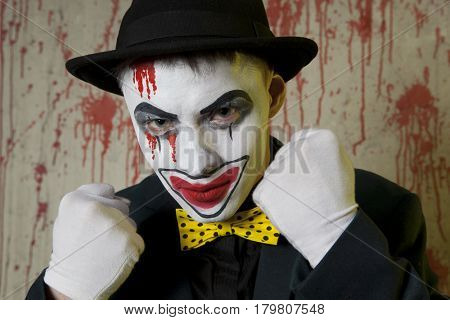 Scary evil clown boxer wearing a bowler hat on wall background