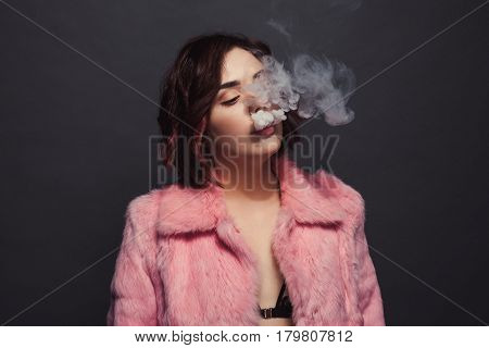 Glamour woman wearing pink jacket having a smoke on the black background.