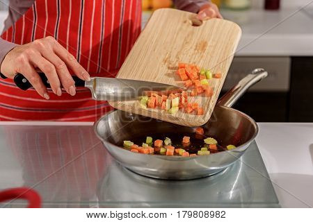 Close up of female hands putting chopped vegetables into frying pan. Woman is holding board and knife