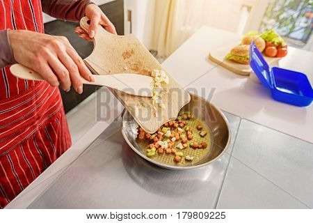 Close up of arms of woman pouring out cup onion from board into frying pan