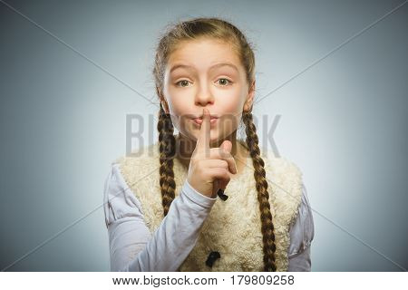 girl placing finger on lips asking shh, quiet, silence on gray background.