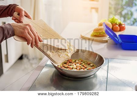 Close up of hands of skillful housewife cooking healthy breakfast in kitchen. She is holding board and putting ingredients into frying pan