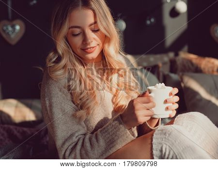 Pretty young woman with eyes closed sitting and holding a coffee cup.