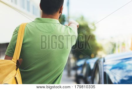 Hipster young man with backpack and map. View from back tourist traveler planning route on background sun city and pointing hand route. Person hiker visiting the sights on backdrop summer street mockup