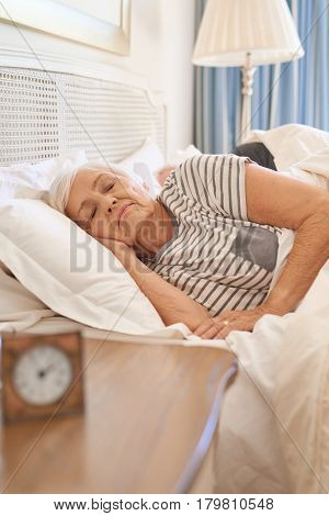 Senior woman sleeping soundly while lying in bed next to an alarm clock in the morning with her husband asleep behind her