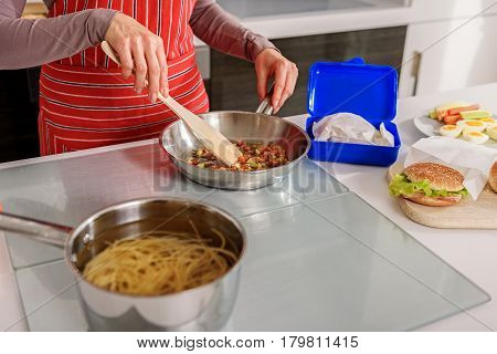 Close up of hands of skillful housewife cooking pasta in kitchen. She is standing and holding frying pan