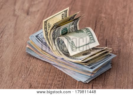 Stack Of Us Dollars In Cash In Wooden Desk.