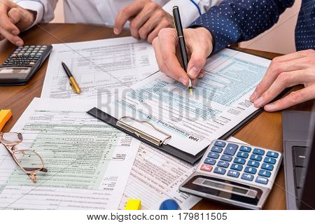 Two Men Calculates Income Tax Form. Tax Form Concept.
