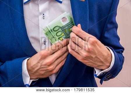 Businessman Putting 100 Euro Bills In His Pocket.
