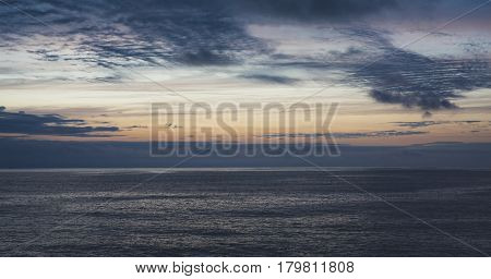 Clouds sky and sunlight sunset on horizon ocean. Silhouette person on background seascape dramatic atmosphere rays sunrise. Relax view waves water sea mockup nature evening concept perspective sunrise