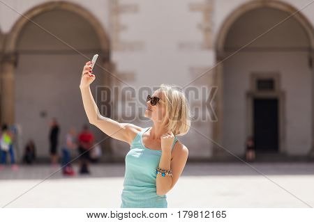 Female traveler on the background of Arcades in Wawel Castle in Cracow. Poland. Renaissance. A woman is photographed on her phone against the background of the castle courtyard