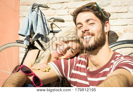 Happy hipster couple taking selfie at old town trip with vintage bicycle - Fun concept with alternative fashion city travelers - Handsome boyfriend with caucasian girlfriend - Warm bright vivid filter