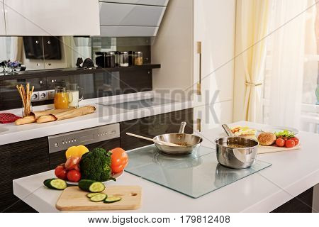 Modern domestic kitchen during breakfast preparation. Fresh vegetables, frying pan and pot with pasta on table