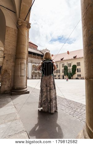 A woman in a blue T-shirt with a backpack on her back is standing in the courtyard of the Wawel Castle in Cracow and enjoying the architecture of the building. Poland. Renaissance.