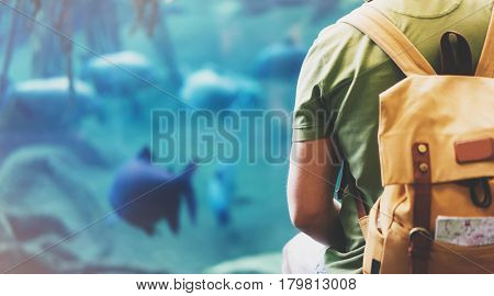 Hipster man with yellow backpack map. View from back tourist traveler on background blue sea aquarium. Person hiker guy sitting in oceanarium museum Barcelona and looking on fish blank blur mockup