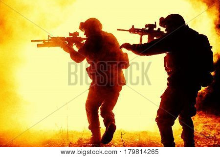 Black silhouettes of pair of soldiers in the smoke fire moving in battle operation. One raising hand to warn another