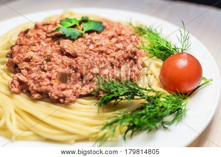 hot spaghetti with red meat sauce , cherry tomoto and parsley on big white plate on a wood table . Health food concept