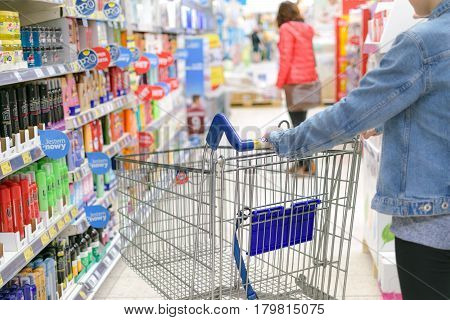 Nowy Sacz Poland - March 29 2017: Young woman pushing shopping cart through front of aisle with a variety of personal care products in a Tesco Hypermarket.