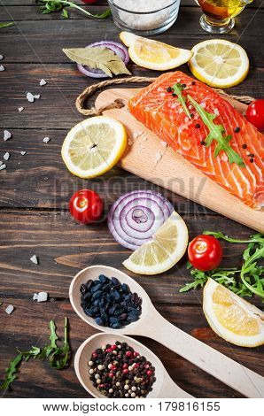 Delicious portion of fresh salmon fillet with aromatic herbs spices and vegetables - healthy food diet or cooking concept.