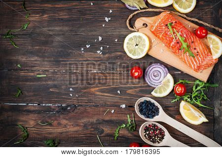 Delicious portion of fresh salmon fillet with aromatic herbs spices and vegetables - healthy food diet or cooking concept. Top view and copyspace.