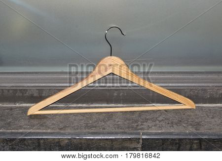 A wooden clothes hanger against a wall