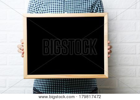 Male Hands Holding Wooden Frame On Brick Wall Background