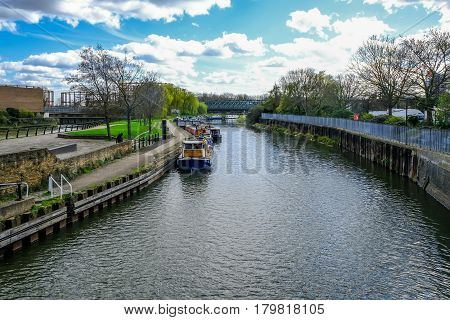 Canal, River Lee and railway bridge, shows longboats moored at the side of the water.