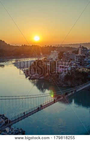 View of River Ganga and Lakshman Jhula bridge at sunset with a blue sky and colorful houses. Rishikesh. India. HDR image