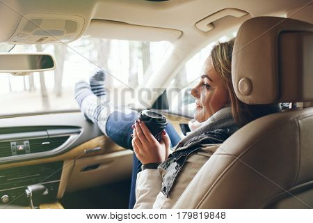 Woman traveler sitting in a car on passengers seat with feet in warm socks on car dashboard. Drinking take away coffee on road. Road trip. Freedom travel concept. Sun light flair effect
