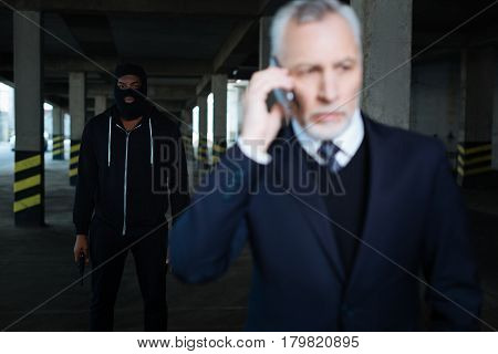 Dangerous criminal. Serious dangerous male kidnapper wearing a mask and holding a handgun while kidnapping a businessman