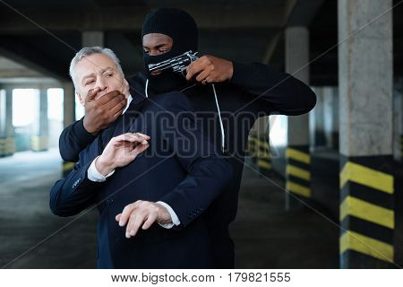 Do not speak. Aggressive dangerous afro american criminal holding a gun and covering the mouth of a businessman while kidnapping him