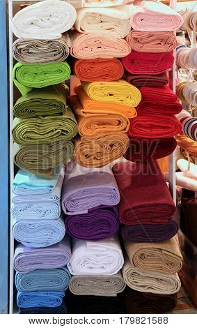 shelf with several rolls of colored fabric in the store for tailors