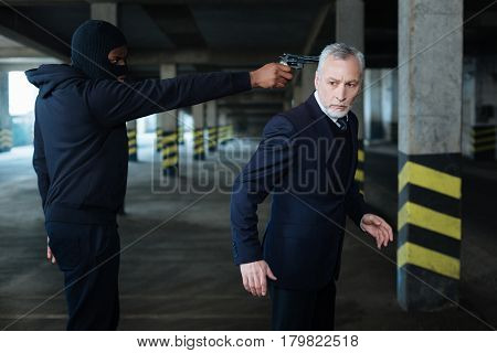 Do not move. Handsome anxious nice businessman standing at gunpoint and trying not to move while being in danger