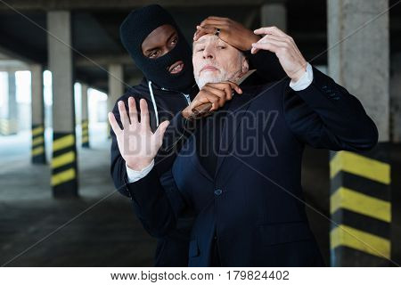 Aggressive behaviour. Aggressive ruthless male criminal wearing a mask and holding a knife while trying to kill a businessman