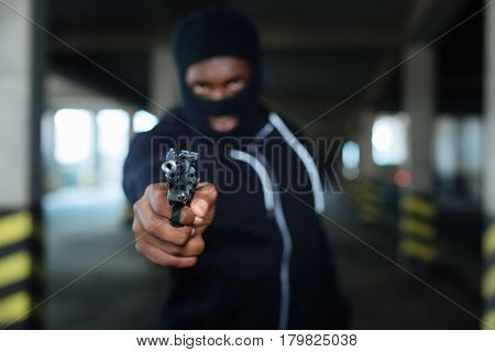 You are the target. Selective focus of a handgun muzzle being aimed at you while being in hands of a dangerous criminal