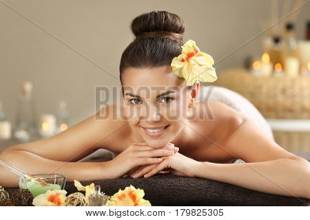 Beautiful young woman lying on massage table in spa salon