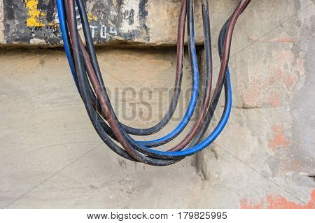 Closeup of colorful electrical cords hanging down from tltctrical board on wall of building