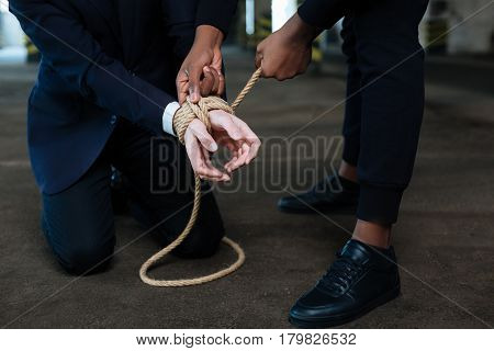 You will not escape. Dangerous afro american male criminal standing above his victim and binding his hands while holding him hostage