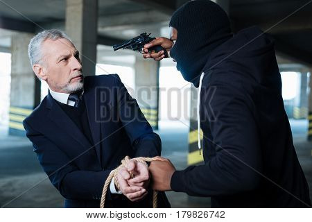 Stay here. Aggressive ruthless hardened criminal holding the rope and threatening a businessman while committing a crime