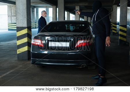 Stay here. Good looking nice handsome businessman standing near his car and intending to get in it while becoming a crime victim