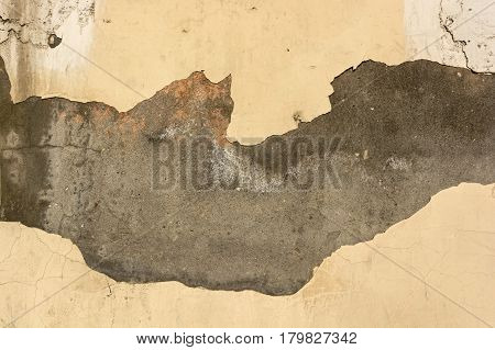 Abstract texture of wall covered with obsolete damaged beige cement plaster