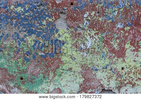Abstract texture of wall covered with obsolete colorful cement plaster