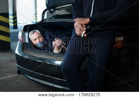Successful assault. Nice calm adult man holding a cigarette and smoking it while enjoying leaning on the car boot