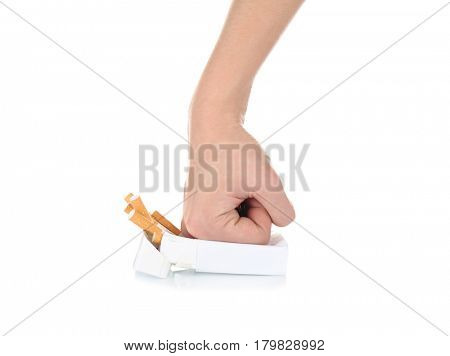 Human hand crushing cigarettes on white background