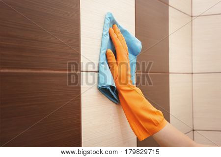 Female hand cleaning tiled wall with rag