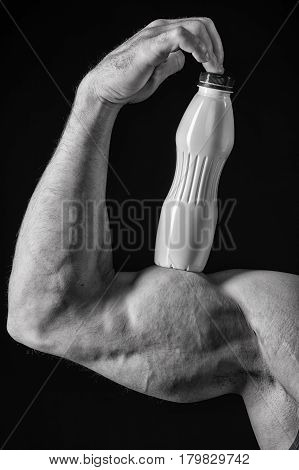 male hand of bodybuilder man or sexy muscular guy with athlete body biceps and triceps training sport in gym holds thermo mug bottle or flask with drink black and white